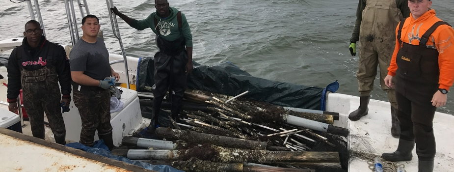 Five volunteers stand in a boat loaded with debris.