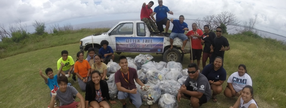 Participants pose with their haul from a beach cleanup as part of the Micronesia Island Nature Alliance's efforts against marine debris.