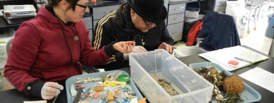 Two teachers sort through a bin of marine debris in a lab.