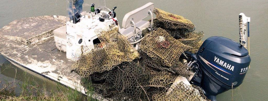 Man standing at the front of his boat with a pile of derelict crab traps piled at the rear.