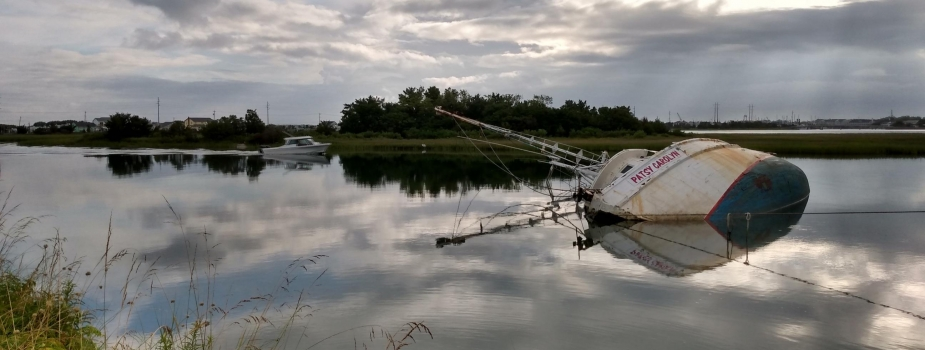 A derelict vessel on its side and partially submerged in the water.