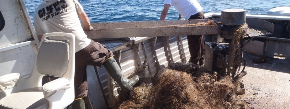 Two people hauling a derelict net onto a boat.