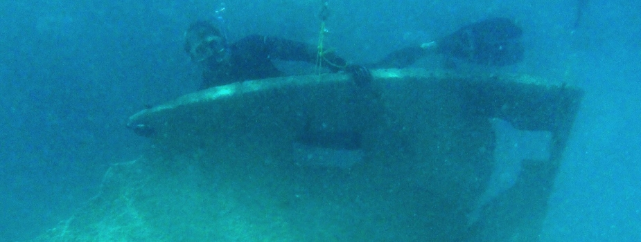 A diver holds a slab of metal removed.