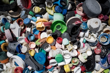 Assorted old plastic bottle caps in a variety of colors, shapes, and types.