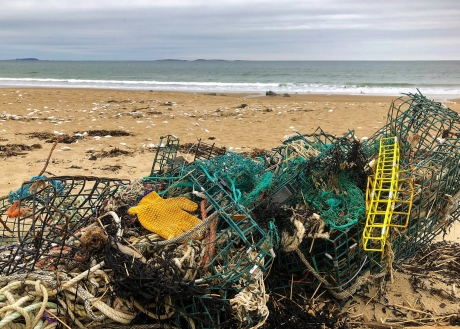 A pile of derelict fishing line, nets, traps, and other debris on a beach.