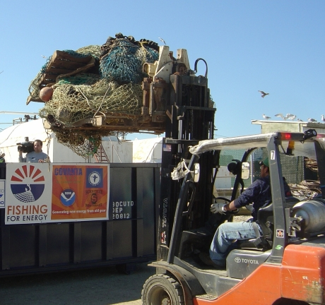 A man disposing of nets in a Fishing for Energy bin with a tractor crane.
