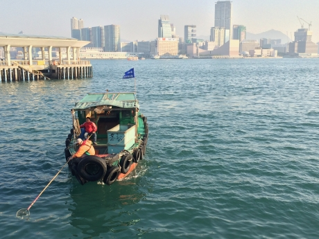 People remove marine debris floating in Hong Kong with nets.