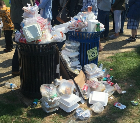 A trash and recycling can overflowing with single-use food containers at an outdoor event.