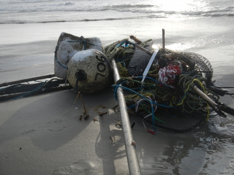 Nets, buoys, and other debris piled on the beach.
