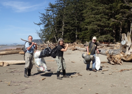 Three people walk on a beach on the Olympic Coast carrying plastic bags full of garbage.