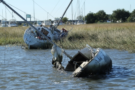 Two abandoned and derelict vessels in a salt marsh.