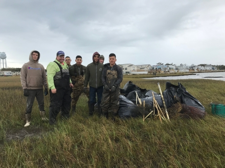 Project participants standing in a marsh alongside bags of collected debris.