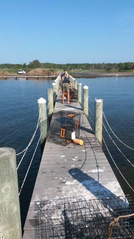 Two people stack crab traps at the end of a dock.