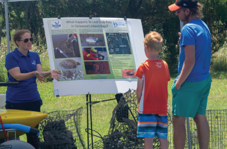 Three people stand around a poster talking about derelict crab traps.
