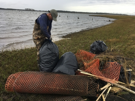 A project participant stands near a pile of debris while securing a bag of collected debris.