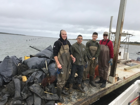 Four project participants stand on a dock next to bags of collected debris.
