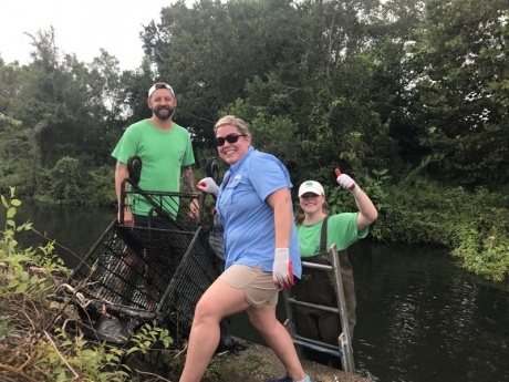 Three project participants pose with a grocery cart found in One Mile Creek.