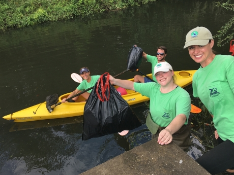 Project participants on shore and in a kayak pose with bags of debris collected from One Mile Creek.