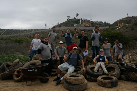 Group of people cheering on top of a pile of tires.