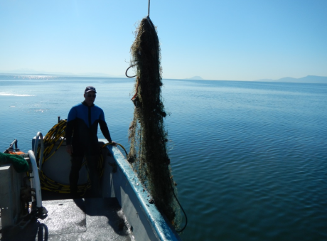 A person on a boat standing next to a derelict net.