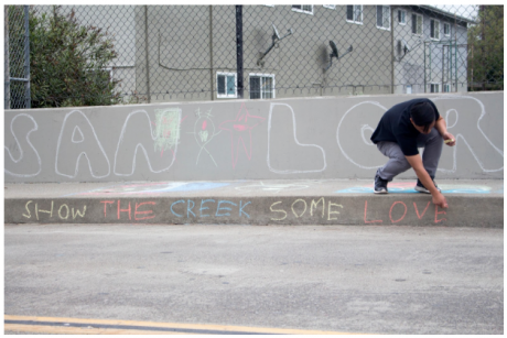 """A student writes """"show the creek some love"""" on the sidewalk."""