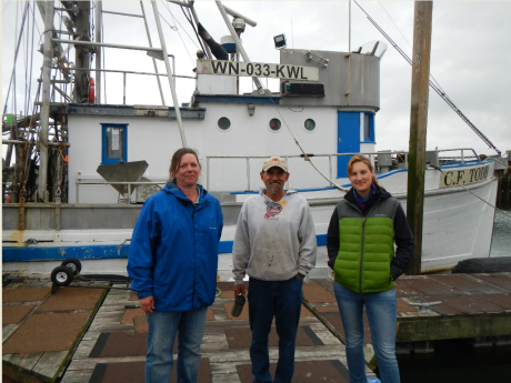 Three people standing in front of a boat.
