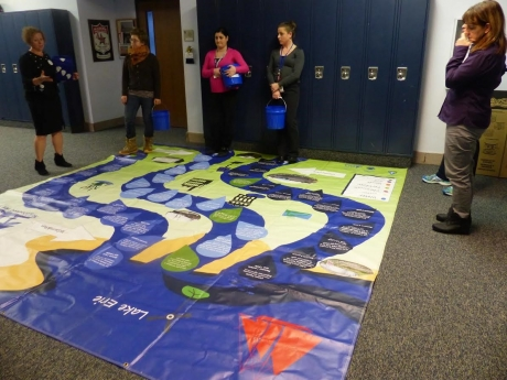 Teachers around a watershed floor mat.