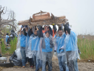 Workers lift heavy debris from beach.