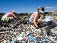 Two people cleaning up marine debris from a rocky shore.