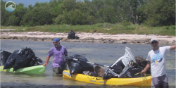 Two people with a canoe clean up garbage from water.