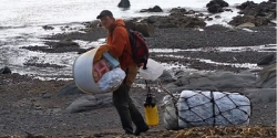 Man hauling large debris items from beach.